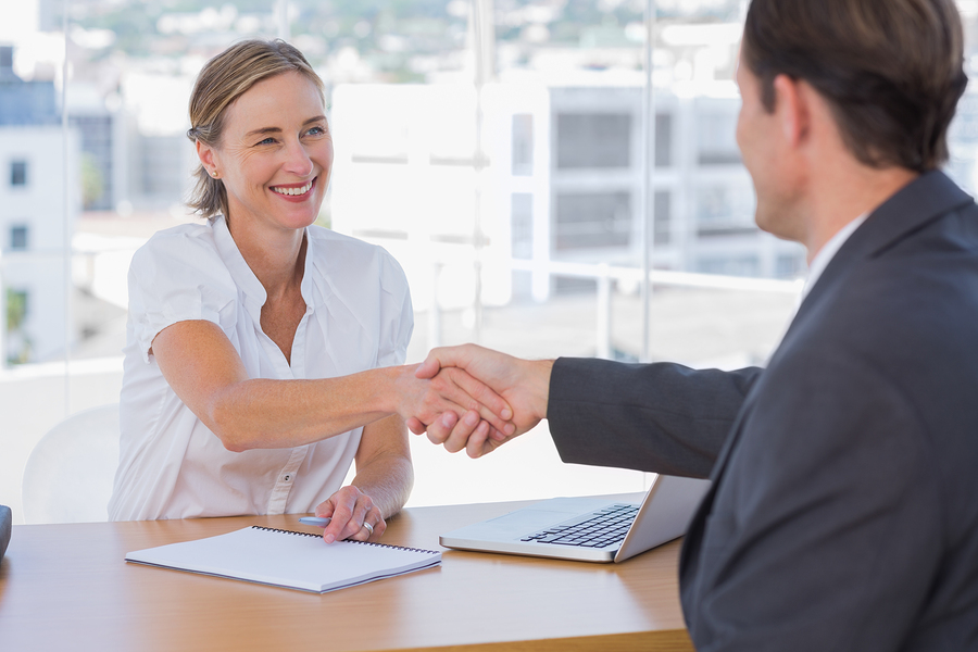 Cheerful interviewer shaking hand of an interviewee during a job